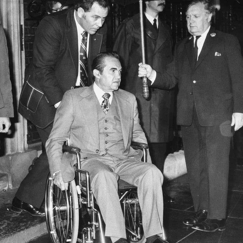 Photo de 1975 montrant le gouverneur de l'Alabama George Wallace, en fauteuil roulant, devant la résidence de la politicienne britannique Margaret Thatcher.