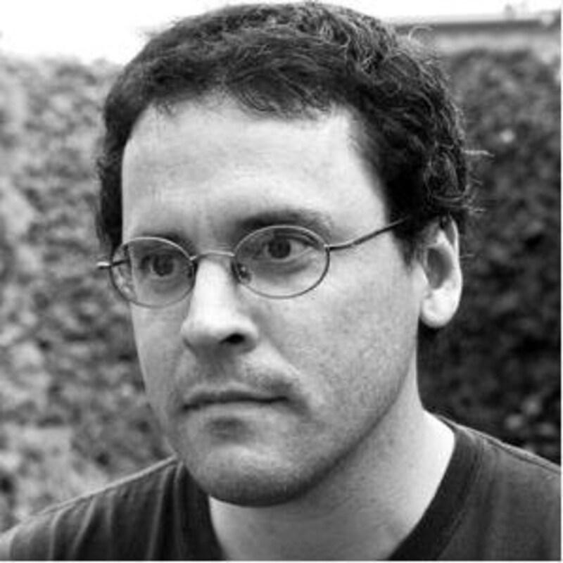 Une photo en noir et blanc de l'auteur, cheveux courts et lunette ovale.