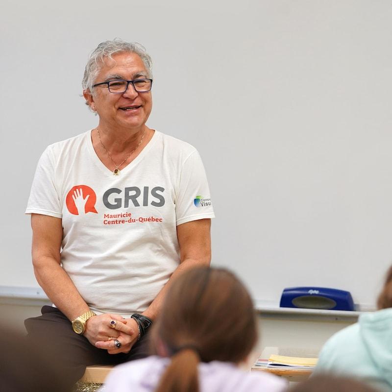 Richard-Alain Senneville assis devant une classe d'élèves.