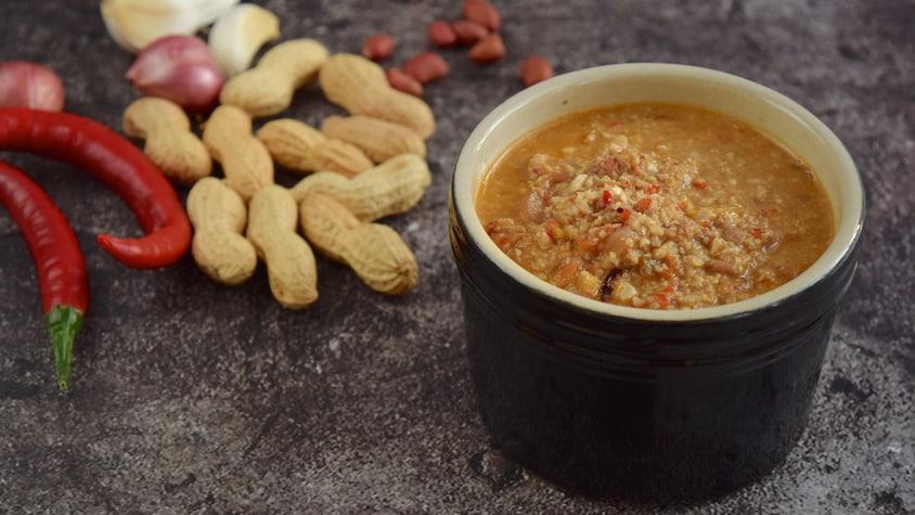 Un bol de marinade aux arachides sur un comptoir déposé à côté de piments, d'arachides et de gousses d'ail.