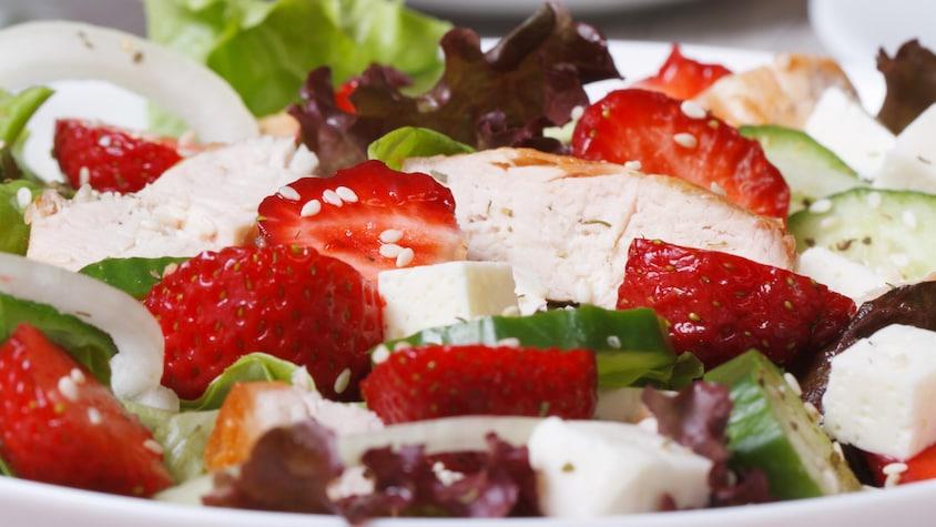 Une salade vu de près avec fraises, concombres, oignon et feta.