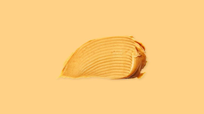 Un peu de beurre d'arachides sur un fond jaune.