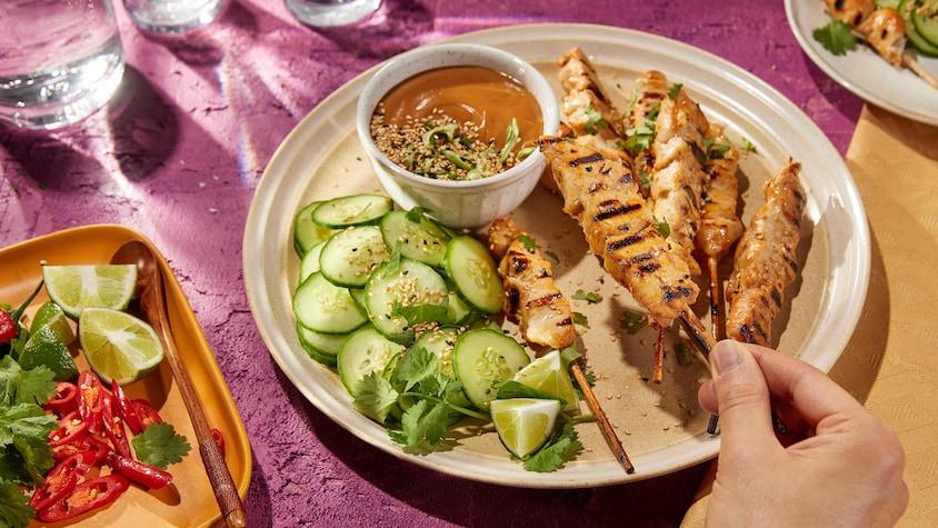 Des brochettes de poulet avec des concombres, de la lime, de la coriandre et une sauce.