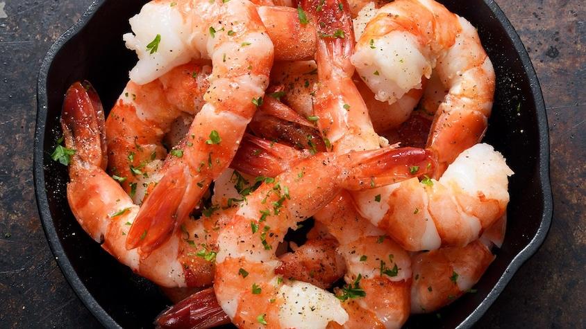 Des crevettes cuites avec leur queues, avec des fines herbes.