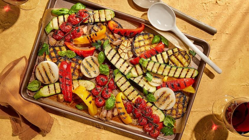 Une plaque de courgettes, de poivrons rouges et jaunes, de tomates en grappe et d'oignons grillés.