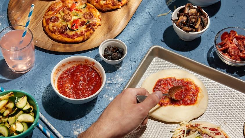 Quelques pizzas garnies sur une planche de bois et des bols de condiments autour.