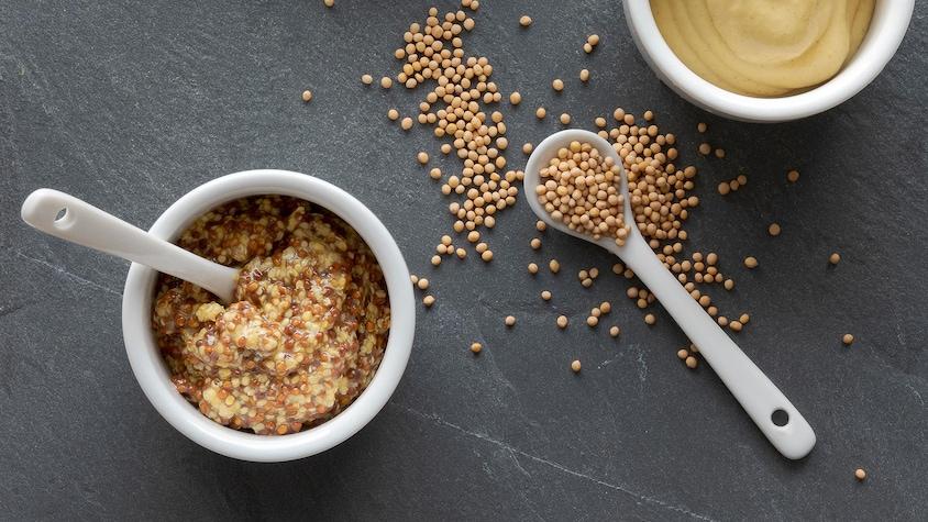 Un petit bol rempli de moutarde en grains et un autre rempli de moutarde liquide.