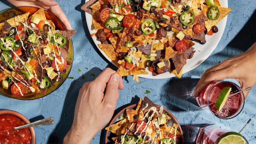Des assiettes de nachos garnis d'olives, de fromage, de tomates et de piments.