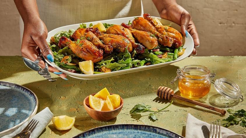 Des pilons de poulet servis sur une salade verte.