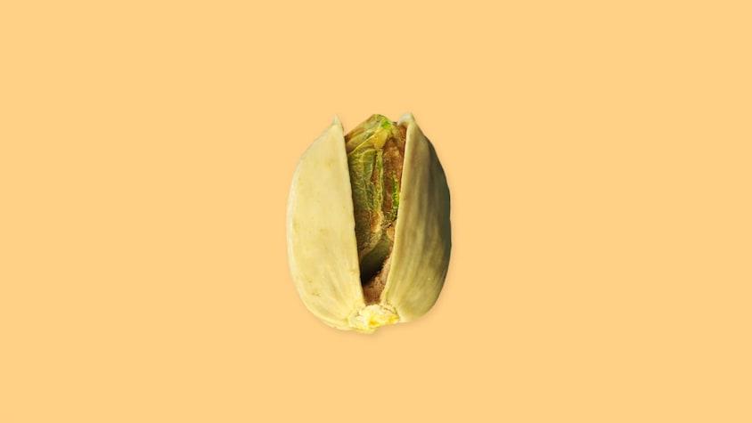 Une pistache sur un fond jaune.