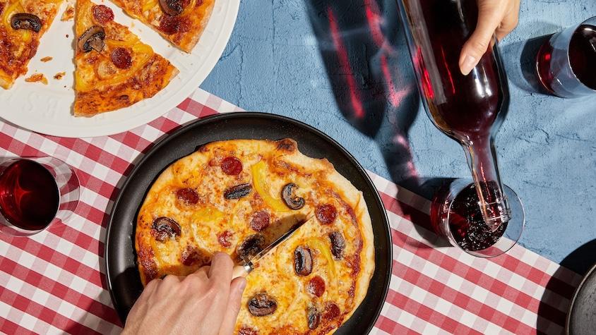 Deux pizzas garnies de pepperonis et de champignons avec des verres de vin rouge.