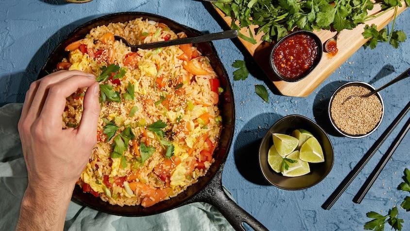 Une poêle remplie de riz frit avec des légumes, de la coriandre et des graines de sésame.