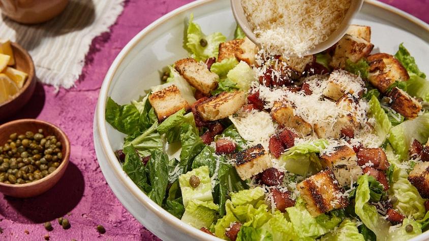 Un gros bol de salade césar avec des croûtons, du fromage parmesan et des lardons.