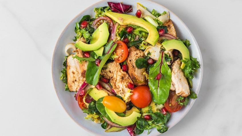 Salade de laitues, tomates, avocat et poulet grillé dans un bol.