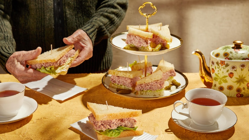 Plusieurs sandwichs au jambon coupés en triangles dans un joli présentoir servis avec du thé.
