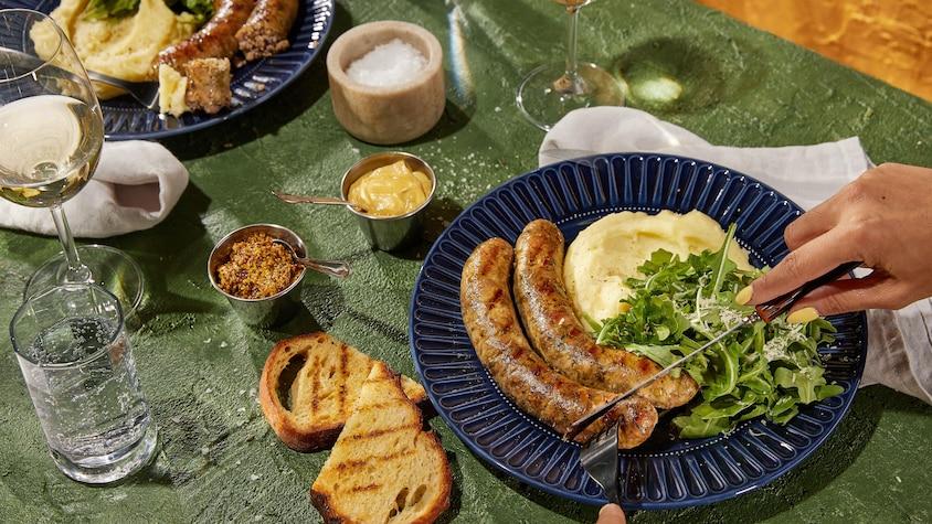 Une assiette contenant deux saucisses, une salade verte et une purée de pommes de terre.