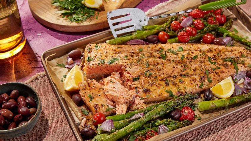 Un gros morceau de saumon grillé sur une plaque avec des tomates, des asperges, des olives et des oignons.