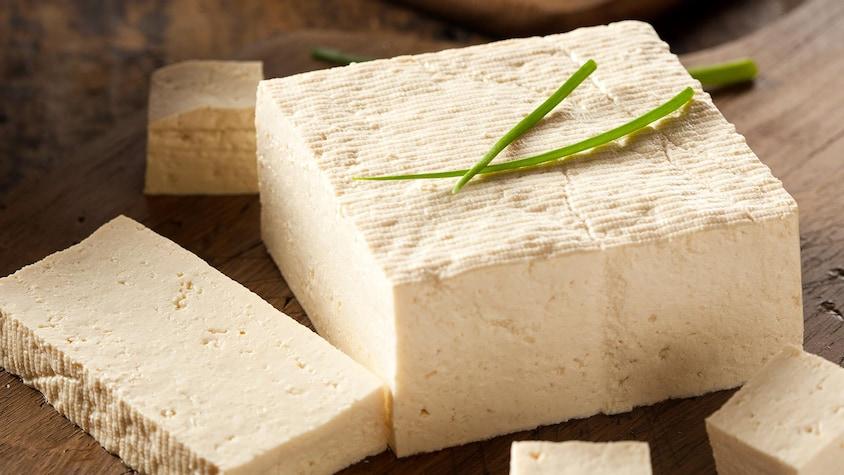 Un bloc de tofu coupé en morceaux sur une planche à découper.