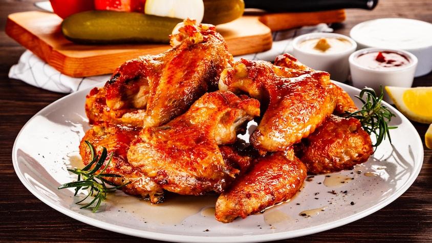 Plusieurs ailes de poulet dans une assiette.