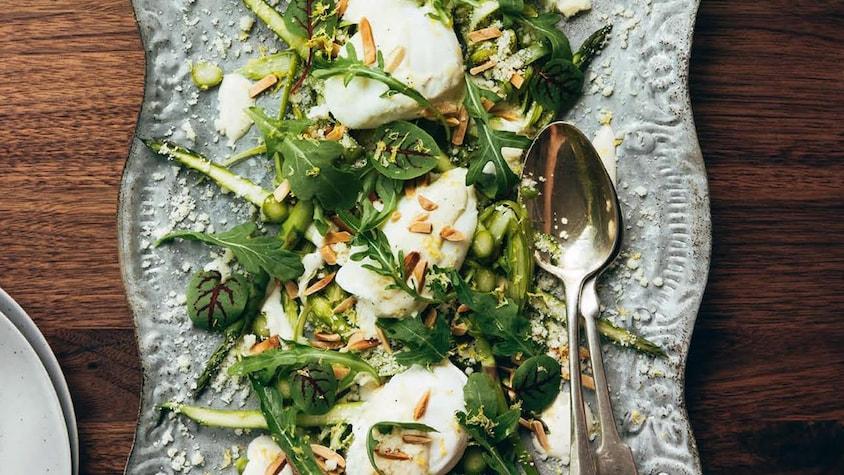 Une assiette de service avec une salade d'asperges aux amandes grillées avec des œufs pochés.