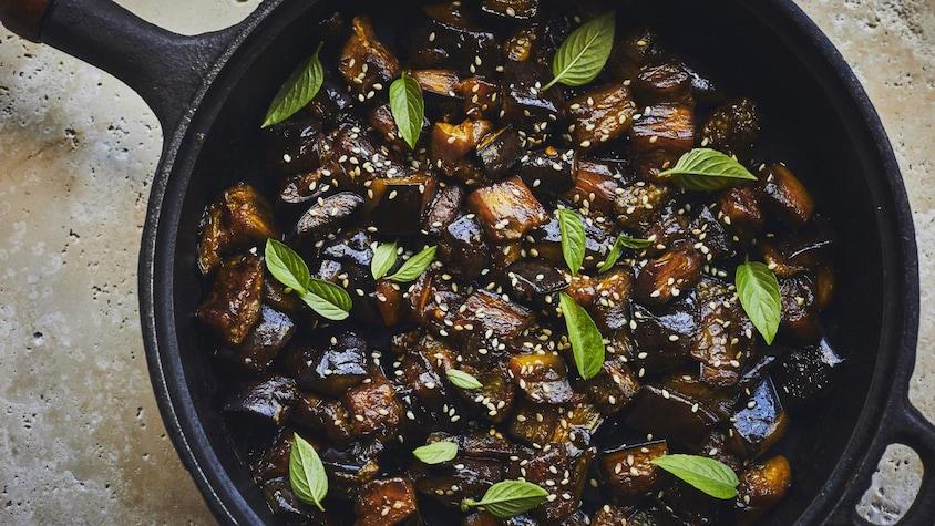 Un plat d'aubergines fondantes à l'asiatique dans une poêle noire.