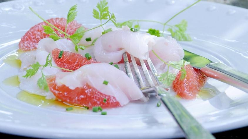 De fines tranches de poisson blanc et des suprêmes de pamplemousse rose parsemés d'herbes fraîches, dans une assiette blanche.