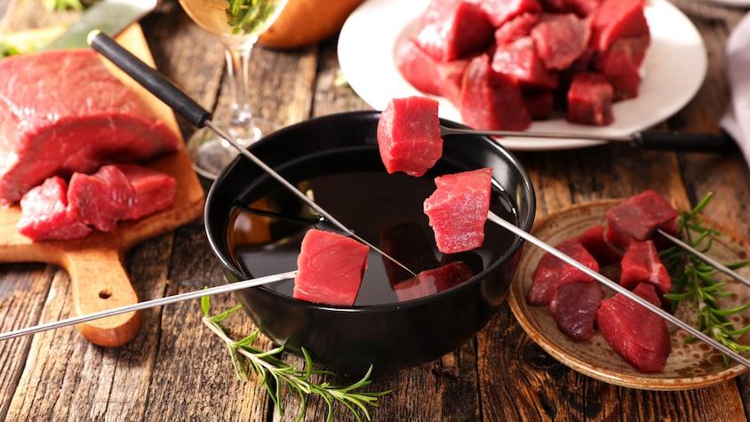Une fondue chinoise, avec des cubes de viande, du bouillon et des fourchettes à fondue.
