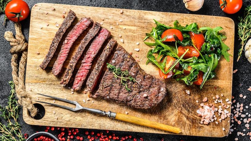 Une bavette de bœuf et une salade sur une planche à découper.