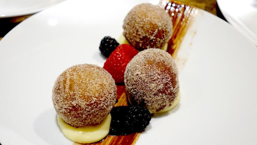 Trois beignets déposés sur de la crème accompagnés de fraises et de mûres.