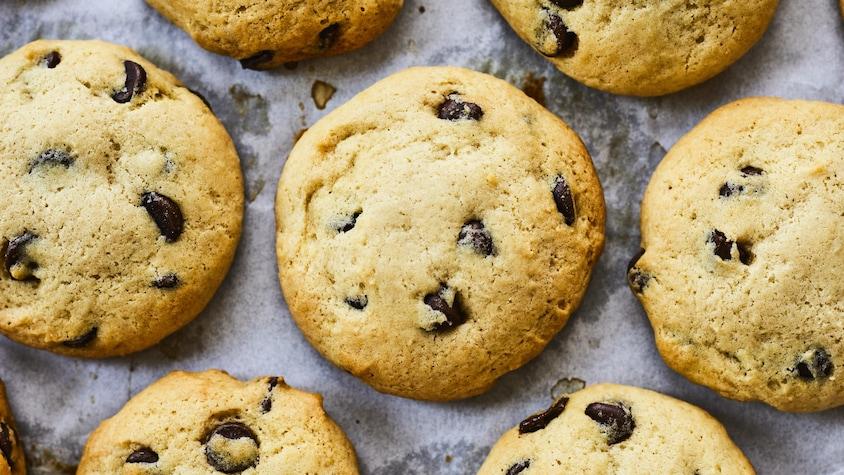 Plusieurs biscuits aux pépites de chocolat étalés sur un papier parchemin.
