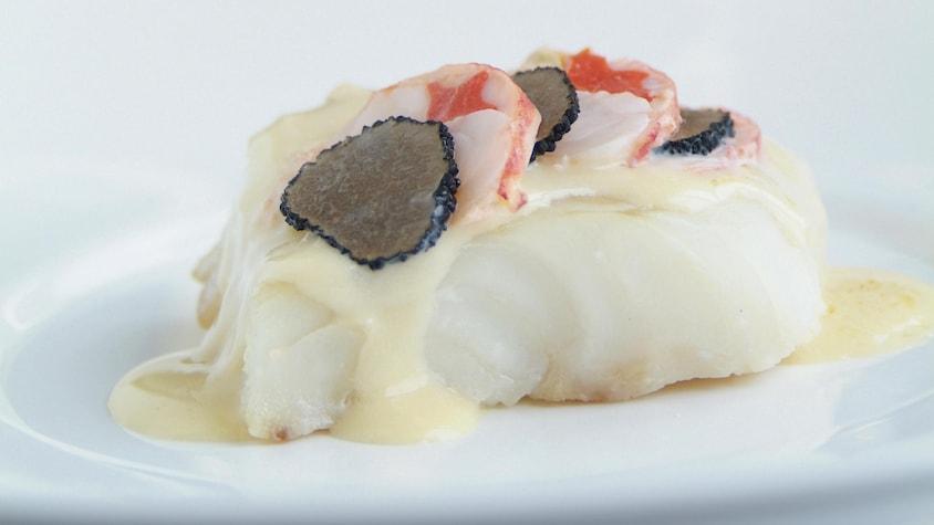 Un morceau de turbot recouvert de sauce, de homard et de truffe dans une assiette blanche.