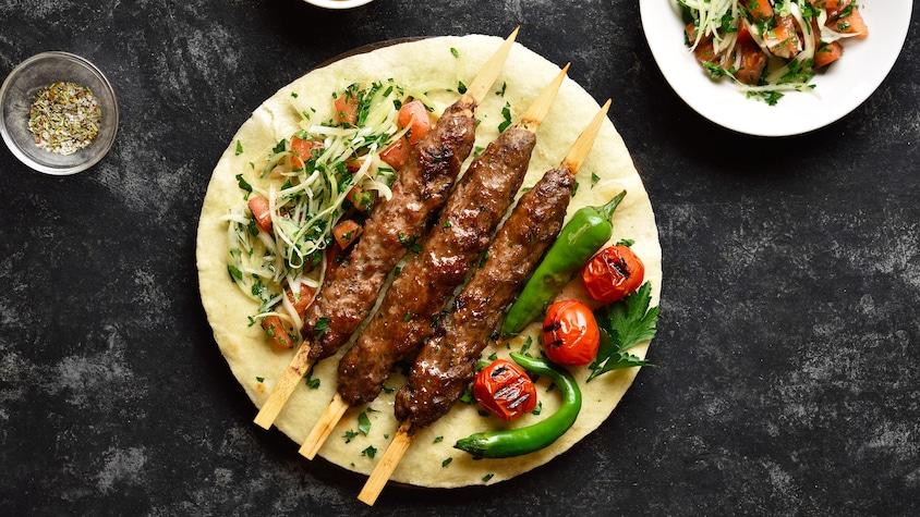 Trois brochettes d'agneau déposées sur un pain pita avec des légumes et un peu de salade.