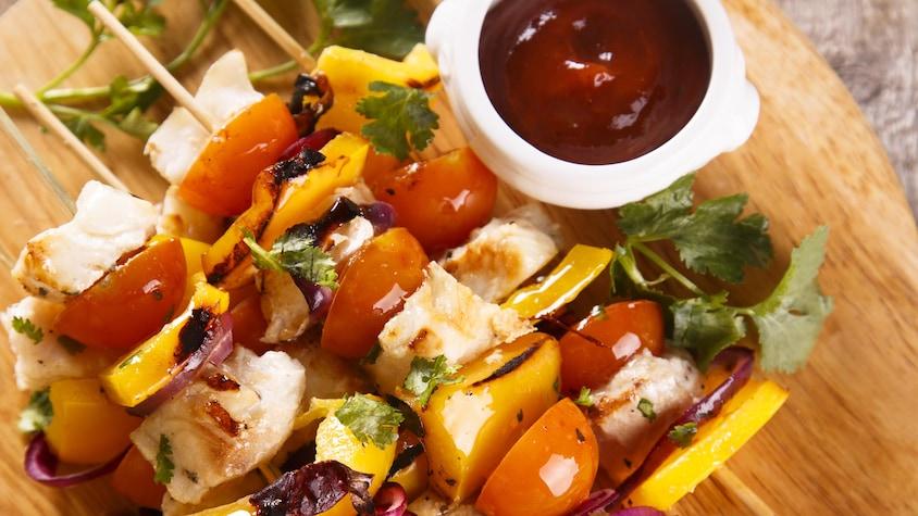 Des brochettes de poisson sur une planche en bois avec un petit bol de sauce.