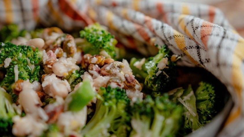 Un bol de salade de brocoli avec des haricots blancs, des pistaches et du parmesan.