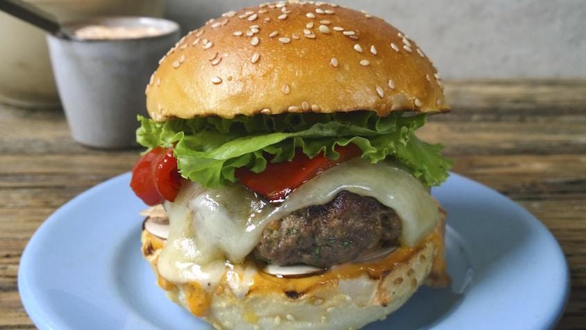 Un burger de veau dans une assiette bleu.