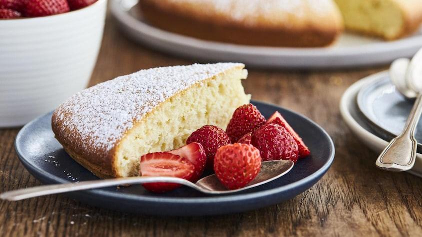 Un cake avec du sucre en poudre servi avec des fraises dans une assiette.