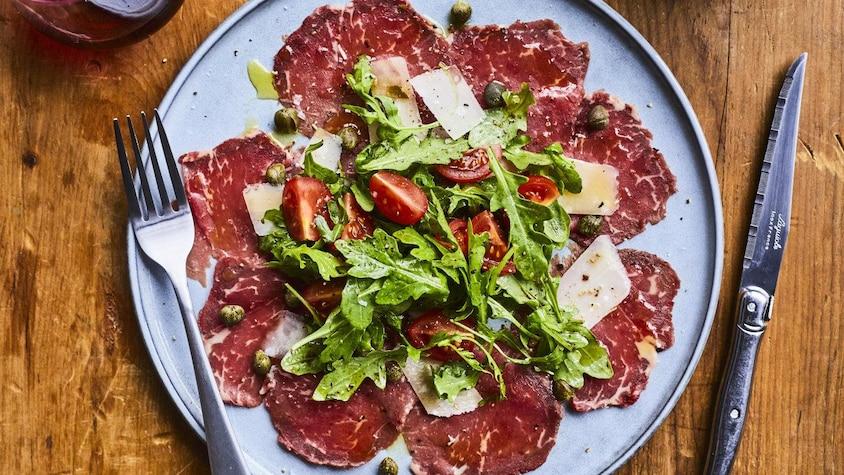 Une assiette de carpaccio de bœuf garni de câpres, de feuilles de roquette, de copeaux de parmesan et de tomates cerises.