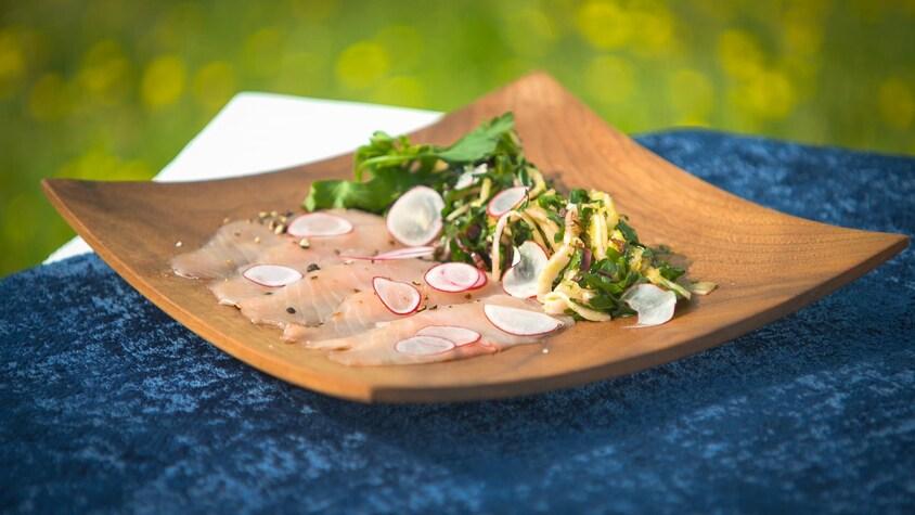 Plusieurs tranches de carpaccio de ouananiche accompagnées d'une salade de fenouil et de bette à carde.