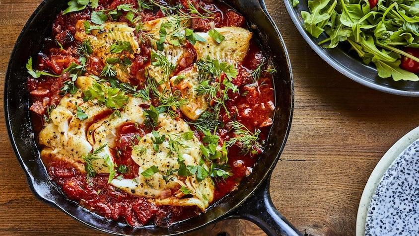 Un poêlon d'aiglefin aux tomates et au chorizo sur une table.