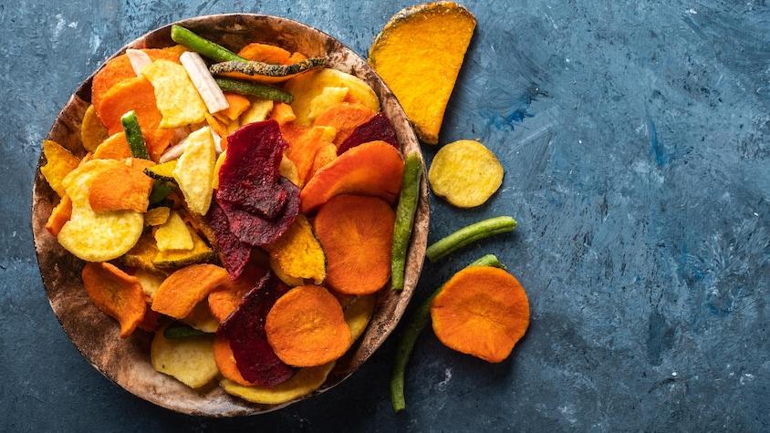 Un bol rempli de croustilles de légumes de plusieurs couleurs différentes.