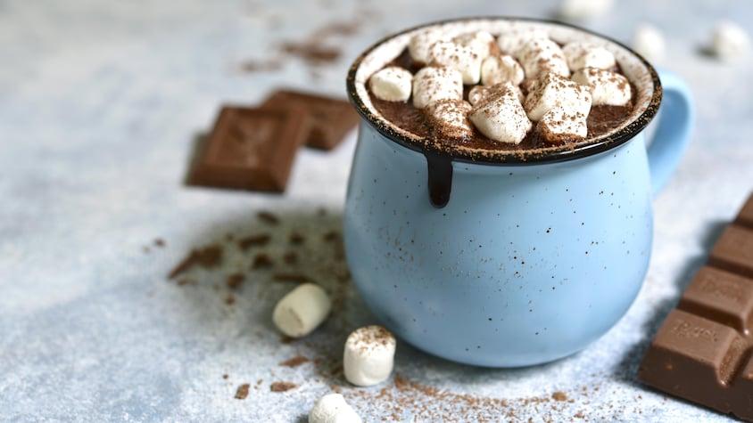 Une tasse bleue remplie de chocolat chaud avec plusieurs petites guimauves.