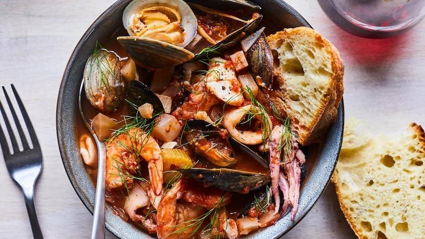 Une soupe de fruits de mer dans un bol accompagnée d'un morceau de pain et d'une cuillère, près d'une fourchette et d'un bout de pain.