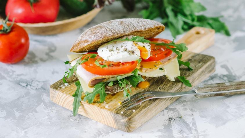 Un sandwich garni avec du jambon, du fromage, de la roquette, des tomates et un œuf à l'intérieur.