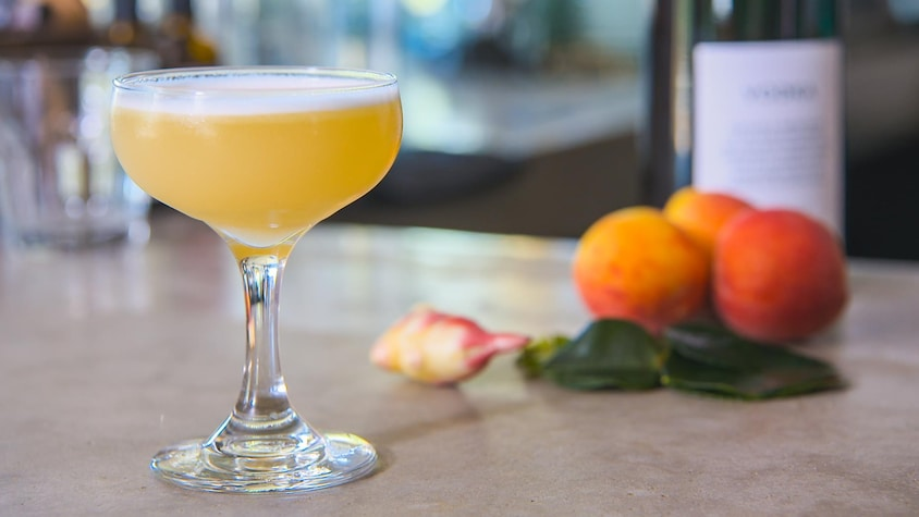 Une cocktail de couleur orangée dans une coupe à champagne Marie-Antoinette.