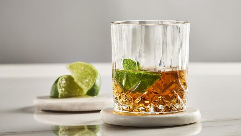 Un punch à l'érable dan un verre accompagné de quartiers de lime.