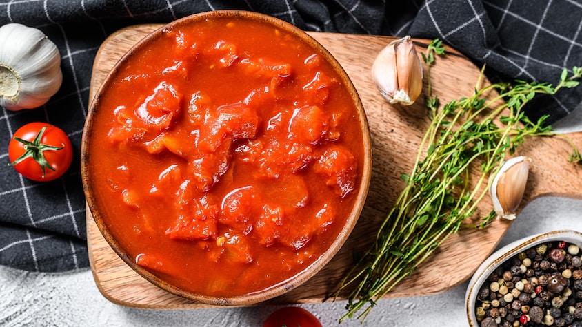 Un bol rempli de tomates concassées déposé sur une planche à découper avec des gousses d'ail et du thym.