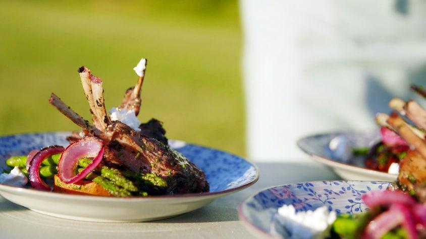 Des côtelettes d'agneau grillées dans une assiette avec des légumes.