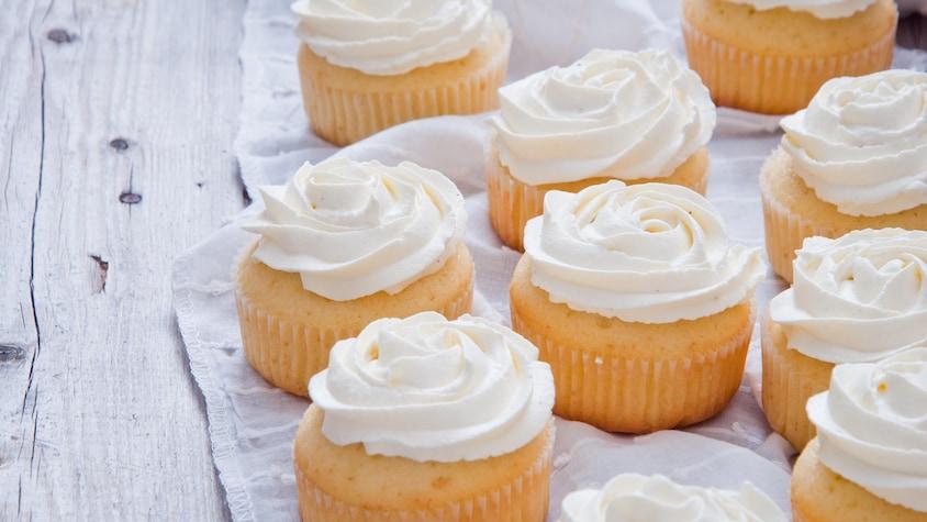 Neuf cupcakes garnis de crème au beurre.