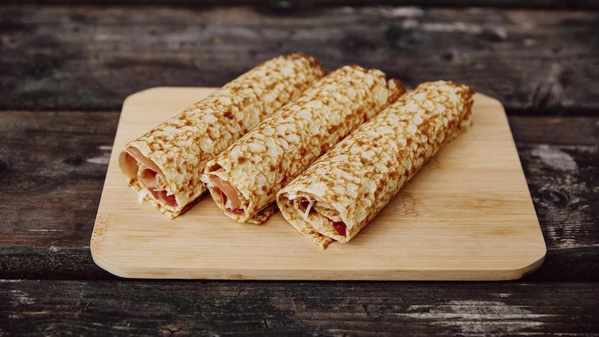 Une planche à découper en bois est déposé sur une table en bois. Sur cette planche à découper, il y a trois crêpes au fromage et au prosciutto.