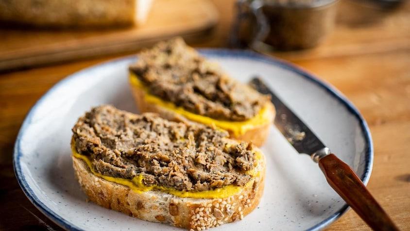 Deux tranches de pain avec de la moutarde et du creton végé dans une assiette.